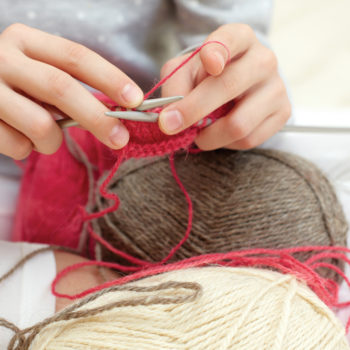 close up image of woman knitting with pink yarn