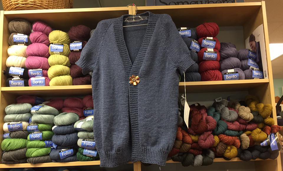 gray knitted sweater hanging up in store