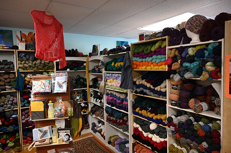 an image of yarn and other assorted knitting supplies and knitting projects on shelves of a knitting store in Connecticut