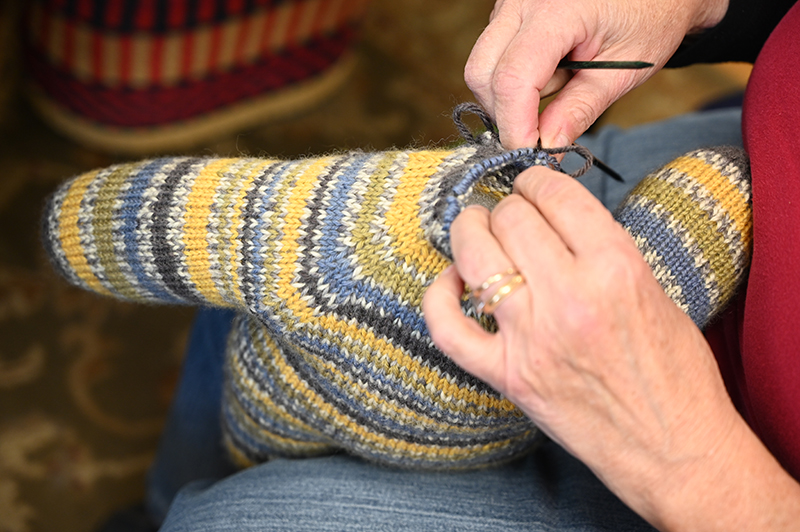 An image of a woman's hands knitting the head of a teddy bear made of yarn at a knitting store in Connecticut